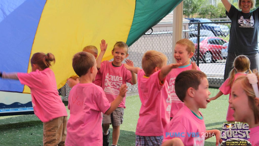 VBS Kids Running and Laughing under a parachute during game time