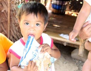 Child from Philippines eating a mobile pack meal