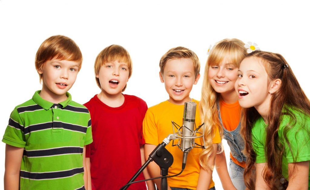 Choir of kids singing in front of a microphone