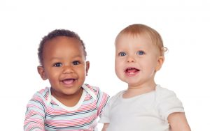 African American and White babies in t shirts sitting together.