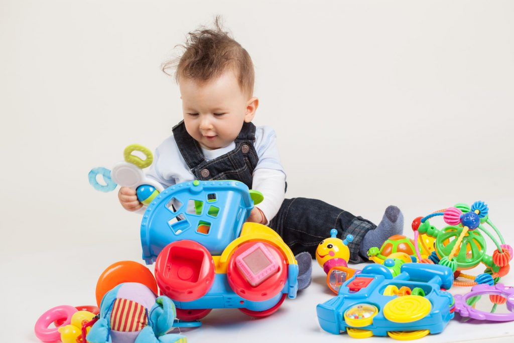 Baby playing with multi colored plastic toys on the floor
